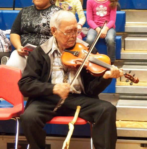 Elder Johnson Moses picks up the Fiddle.