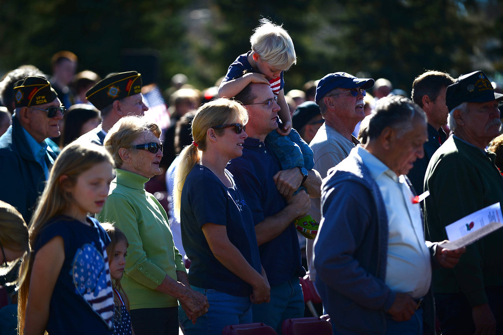 """. Paul Carr holds his son Andrew, 4 on his shoulders while he and his wife Paig sing God Bless America during the 36th annual Remembrance ceremony of Veteran\'s Day at Fort Logan Cemetery in Lakewood, CO  on November 11, 2013. The day was marked with a 21 gun rifle salute, \""""Echo taps\"""" played by buglers and the release of white birds of freedom.  The benediction was given by Jackie Newlander.  (Photo By Helen H. Richardson/ The Denver Post)"""