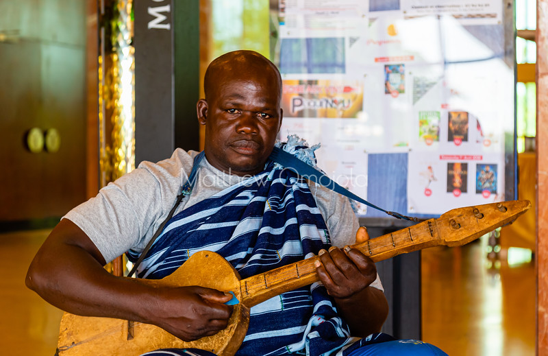 Ivorian man playing local music instrument in Yamoussoukro wearing ivorian dress . Promoting culture.