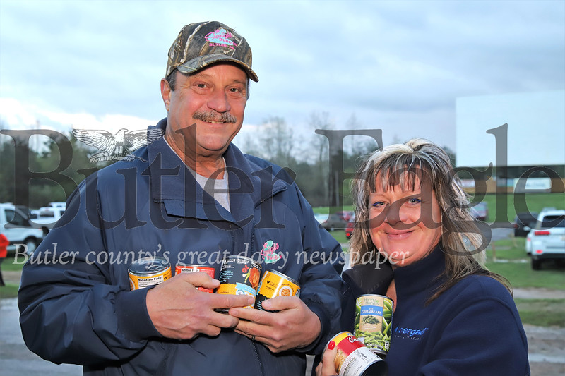 Drive In owners John Manson and Beth Chiesa show some of the cans raised at Friday night's canned food drive.
