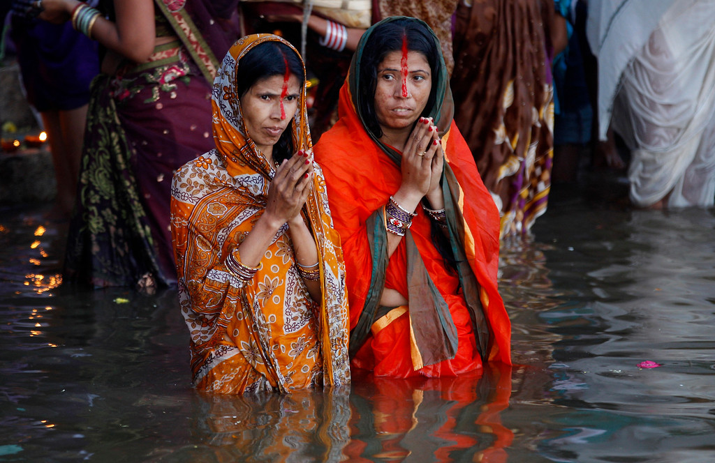 . Hindu devotees stand in water as they perform rituals to the setting sun during Chhath Puja festival in Bangalore, India, Friday, Nov. 8, 2013.  (AP Photo/Aijaz Rahi)