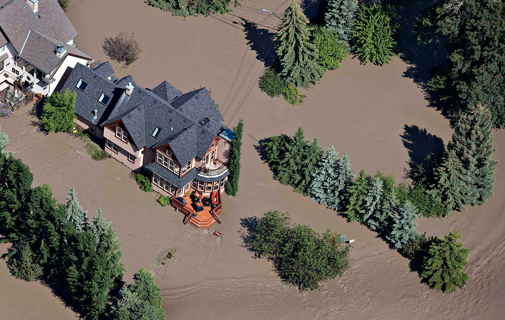 . A house is surrounded by water after the Bow River overflowed its banks nearby into residential areas of Calgary, Alberta June 22, 2013. REUTERS/Andy Clark