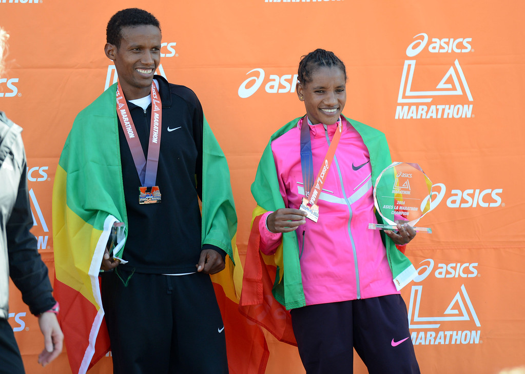 . 2014 ASICS LA Marathon men\'s winner Gebo Burka,left, and women\'s winner Amane Gobena, of Ethiopia, celebrates crosses the finish line in Santa Monica Calif. Gebo Burka with a time of 2: 10: 37 and Amane Gobena with a time of 2: 27:37.   Sunday, March 9,  2014.   (Photo by Stephen Carr / Daily Breeze)