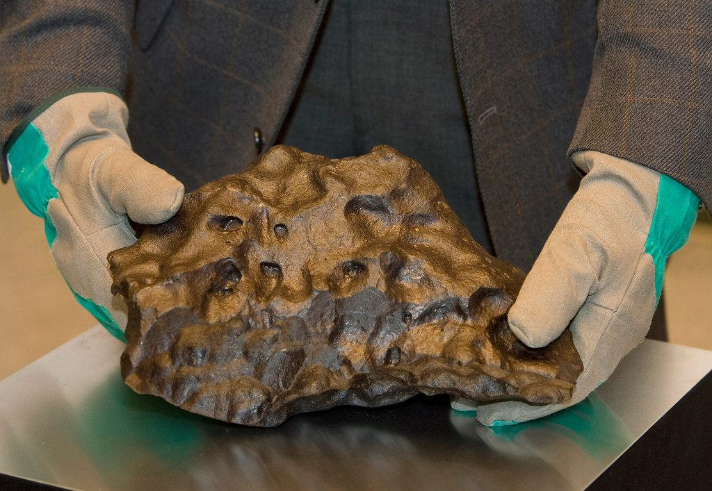 . Expedition leader Georg Delisle poses with a meteorite at the Center of Geology in Hanover, northern Germany, Wednesday, Feb. 6, 2008. The iron stone weights 31kilogram (68.35 pounds). It was found in the Antarctic on Dec, 2, 2007. (AP Photo/Joerg Sarbach)