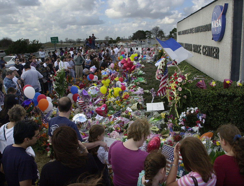 . Mourners visit the main gate of the Johnson Space Center bringing memorial items for the family and crew of space shuttle Columbia in Houston, Sunday, Feb. 2, 2003.  Authorities used horses and satellite gear Sunday to search for more scorched pieces of space shuttle Columbia across the Texas and Louisiana countryside. (AP Photo/Charles Rex Arbogast)