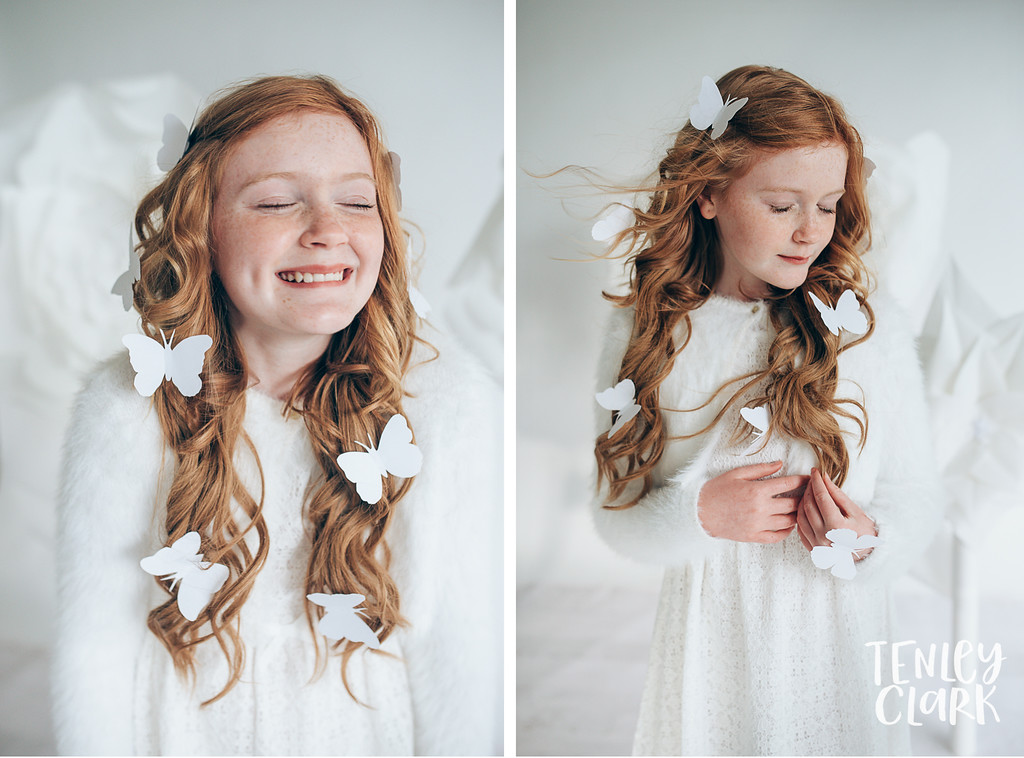 Girl with giant paper flowers and butterflies. Whimsical kid's fashion editorial with giant white paper origami props. Photography by Tenley Clark.