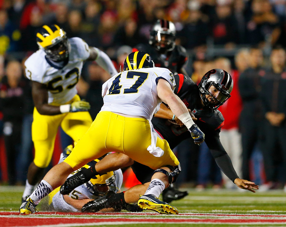 . Rutgers quarterback Gary Nova (10) slides as Michigan\'s Joe Bolden, on ground, and Jake Ryan (47) defend during the first half of an NCAA college football game Saturday, Oct. 4, 2014, in Piscataway, N.J. (AP Photo/Rich Schultz)