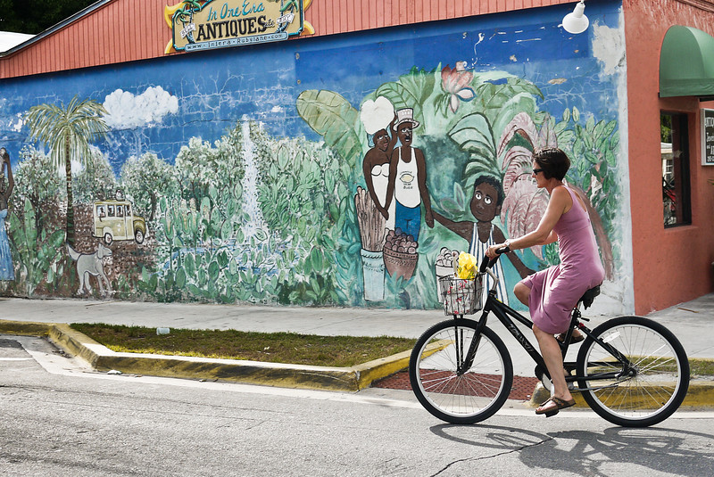 A local woman enjoys a bike ride near a beautiful mural in Old Town Key West, Florida