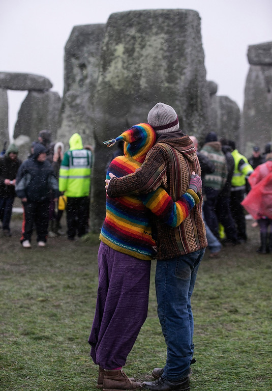 . A couple embrace as druids, pagans and revellers gather in the centre of Stonehenge, hoping to see the sun rise, as they take part in a winter solstice ceremony at Stonehenge on December 21, 2013 in Wiltshire, England.  (Photo by Matt Cardy/Getty Images)