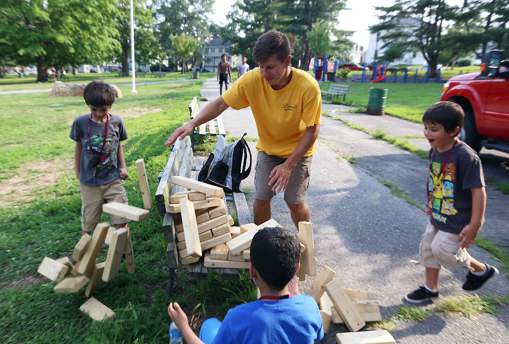 . National Night Out, at North Common, organized by the Lowell Police Department. Clockwise from left, Hermie Sanchez, 8, Andrew Spanos, 18, of Parks & Rec, Hermie\'s brother Navarro Sanchez, 6, and Zabdiel Colon, 10, all of Lowell, watch their Jenga stack collapse. (SUN/Julia Malakie)