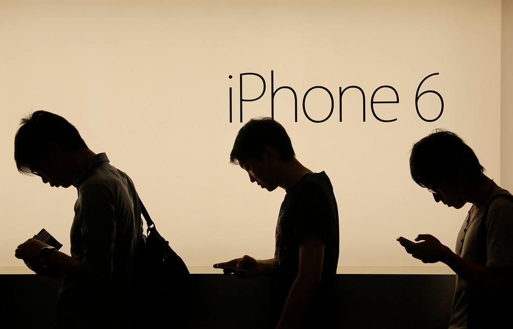 . People wait to buy the new Apple iPhone 6 and 6 Plus devices, outside an Apple store in Hong Kong Friday morning, Sept. 19, 2014. The iPhone 6 and 6 Plus were released on Friday in Hong Kong. (AP Photo/Vincent Yu)