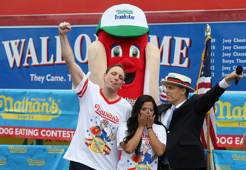 . Joey Chestnut, left, raises his fist after successfully proposing to his girlfriend and fellow competitor Neslie Ricasa, center, alongside master of ceremonies George Shea at the Nathan\'s Famous Fourth of July International Hot Dog Eating contest at Coney Island, Friday, July 4, 2014, in New York. Chestnut won his competition and eighth consecutive contest by finishing 61 hot dogs and buns. (AP Photo/John Minchillo)