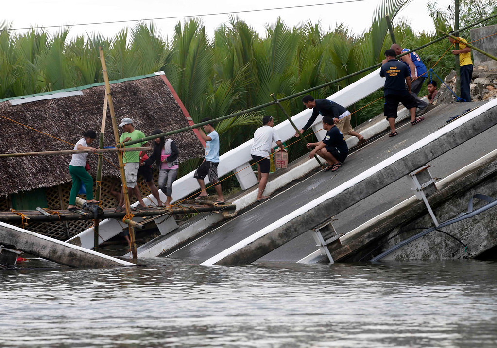. Commuters cross a damaged bridge at Cortes township, Bohol province in central Philippines Thursday Oct. 17, 2013.  (AP Photo/Bullit Marquez)