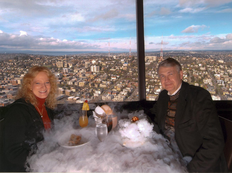 """Pamela & Howard enjoying dessert at the restaurant at the top of the Seattle Space Needle after presenting training in February of 2007.  The """"smoke"""" is from the dry ice used for the special Space Needle dessert."""
