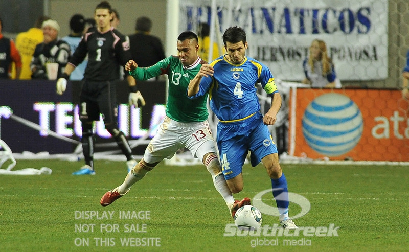 Mexico's Forward Edgar Pacheco (#13) tries to stop Bosnia-Herzegovina's Defencer Emir Spahic (#4) from advancing the ball in Soccer action between Bosnia-Herzegovina and Mexico.  Mexico defeated Bosnia-Herzegovina 2-0 in the game at the Georgia Dome in Atlanta, GA.