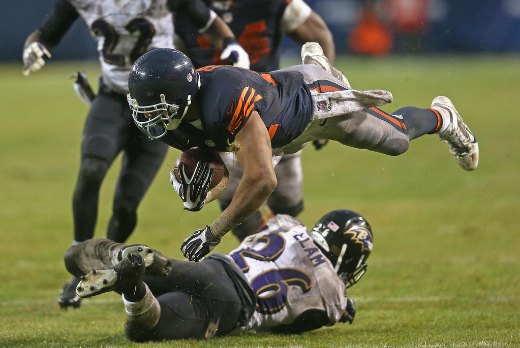 . Matt Forte #22 of the Chicago Bears flies after being hit by Matt Elam #26 of the Baltimore Ravens on a first down run at Soldier Field on November 17, 2013 in Chicago, Illinois. The Bears defeated the Ravens 23-20 in overtime.  (Photo by Jonathan Daniel/Getty Images)