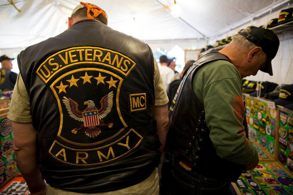. Men look at military badges for sale at a stall during the Rolling Thunder ride in Washington May 26, 2013. The 26th Annual Rolling Thunder is organised to show support for veterans past and present, and those who have fallen in war or missing in action. REUTERS/Joshua Roberts
