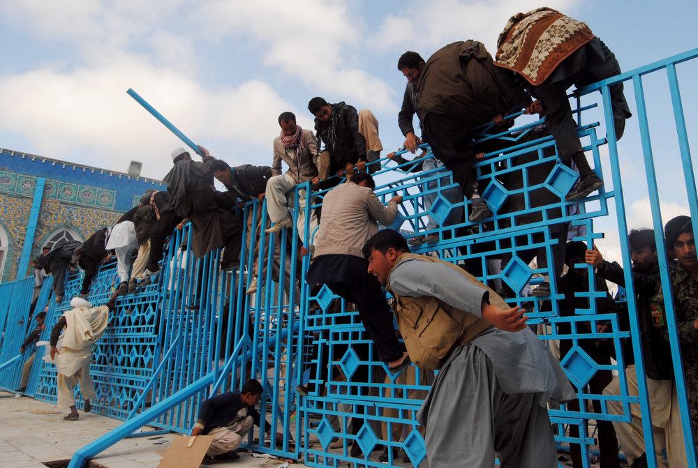 . Afghan men climb over a fence to touch and kiss the Islamic flag being hoisted at the Hazrat-e Ali shrine in Mazar-i Sharif as part of the Afghan new year celebrations on March 21, 2013. Nowruz, one of the biggest festivals of the war-scarred nation, marks the first day of spring and the beginning of the year in the Persian calendar. Nowruz is calculated according to a solar calendar, this coming year marking 1392. FARSHAD USYAN/AFP/Getty Images