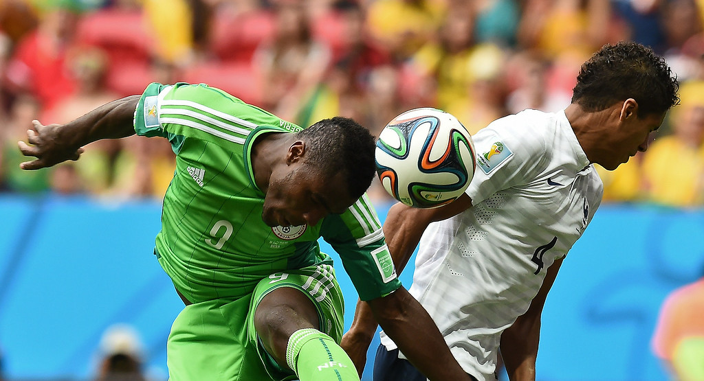 . Nigeria\'s forward Emmanuel Emenike (L) challenges France\'s defender Raphael Varane during the round of 16 football match between France and Nigeria at the Mane Garrincha National Stadium in Brasilia during the 2014 FIFA World Cup on June 30, 2014.  JEWEL SAMAD/AFP/Getty Images