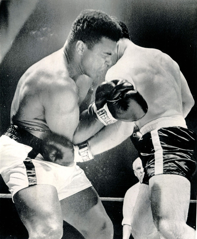 . Cassius Clay (left) grimaces as he takes a left to the body from Canada\'s George Chuvalo midway in their 15-round bout in Toronto Tuesday night.  Clay boasted later that this proved he could take a body punch.  Clay won a unanimous decision. 1966. Credit: AP