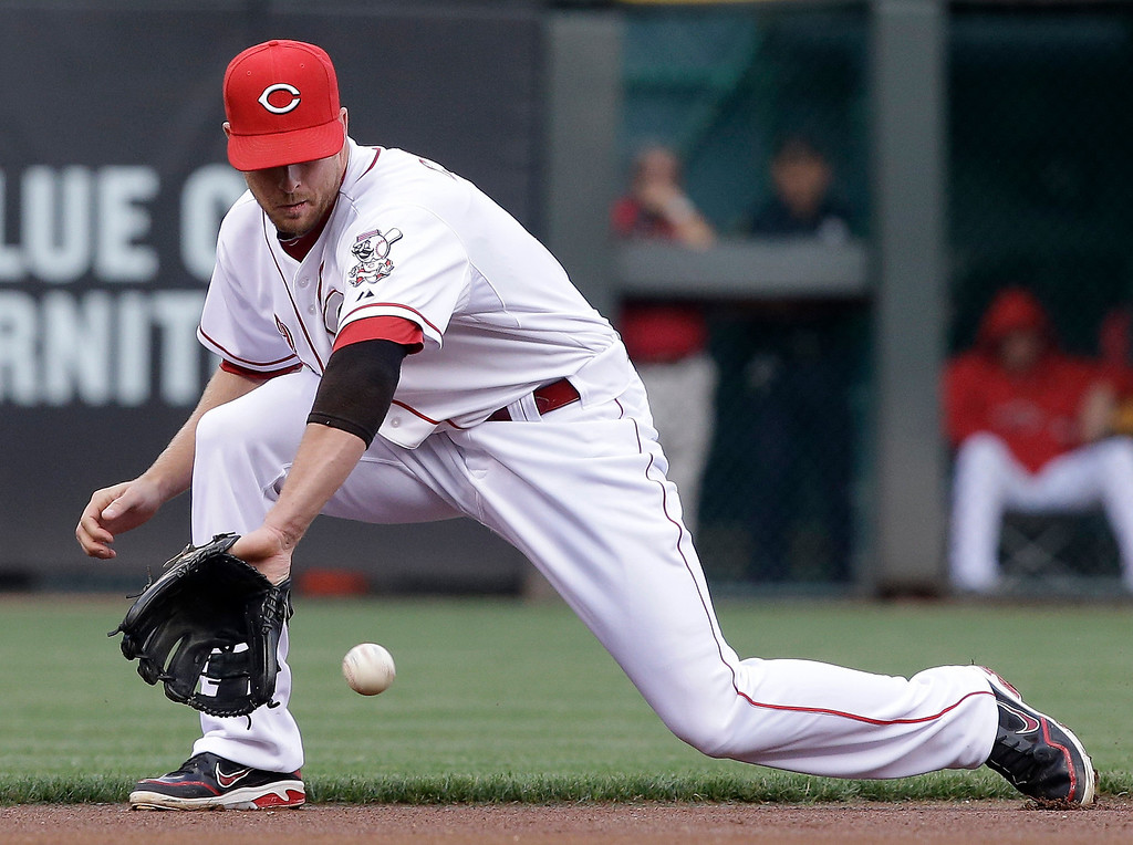 . Cincinnati Reds shortstop Zack Cozart fields a ground ball hit by Colorado Rockies\' Nolan Arenado in the first inning of a baseball game, Monday, June 3, 2013, in Cincinnati. Cozart threw Arenado out at first. (AP Photo/Al Behrman)