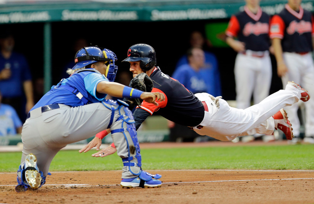 . Cleveland Indians\' Yan Gomes dives into home as Kansas City Royals catcher Salvador Perez waits for the ball in the third inning of a baseball game, Friday, Aug. 25, 2017, in Cleveland. Gomes scored on a one -run double hit by Giovanny Urshela. (AP Photo/Tony Dejak)