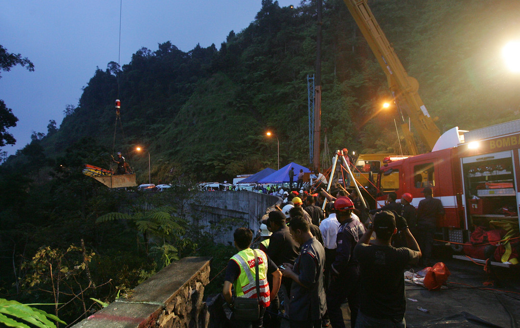 . Malaysian emergency services personnel lift a body of one of the passenger after a bus carrying tourists and local residents fell into a ravine near the Genting Highlands, about an hour\'s drive from Kuala Lumpur, Malaysia, Wednesday, Aug. 21, 2013.   (AP Photo)