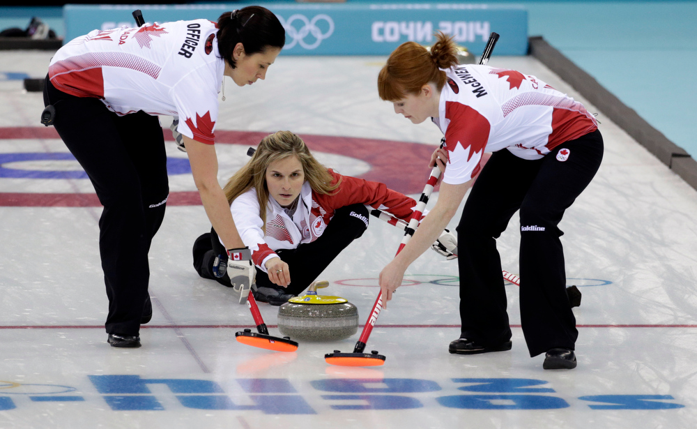 . Canadaís skip Jennifer Jones, center, delivers the final rock to her sweepers Jill Officer, left, and Dawn McEwen to defeat Sweden in the women\'s curling gold medal game at the 2014 Winter Olympics, Thursday, Feb. 20, 2014, in Sochi, Russia. (AP Photo/Robert F. Bukaty)
