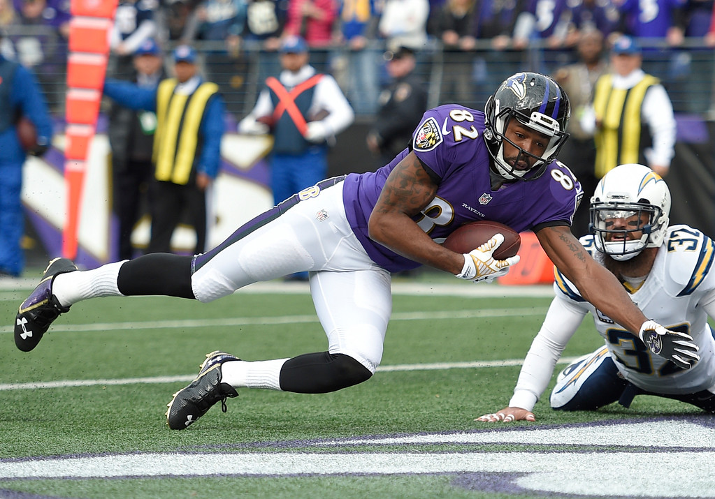 . Baltimore Ravens wide receiver Torrey Smith (82) makes a catch for a touchdown in front of San Diego Chargers free safety Eric Weddle in the first half of an NFL football game, Sunday, Nov. 30, 2014, in Baltimore. (AP Photo/Nick Wass)