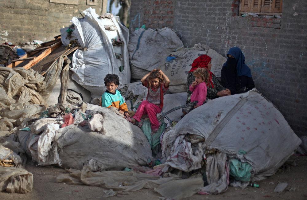 . Palestinian refugees sit on plastic sacks of garbage outside a house in Gezirat al-Fadel village, Sharqiya, about 150 kilometers (93 miles) east of Cairo, Egypt.  (AP Photo/Khalil Hamra)