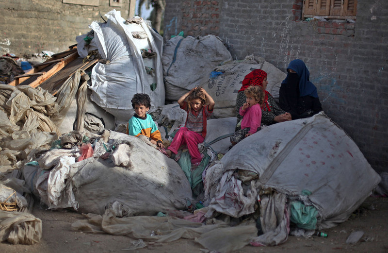 . Palestinian refugees sit on plastic sacks of garbage outside a house in Gezirat al-Fadel village, Sharqiya, about 150 kilometers (93 miles) east of Cairo, Egypt.  (AP Photo/Khalil Hamra)