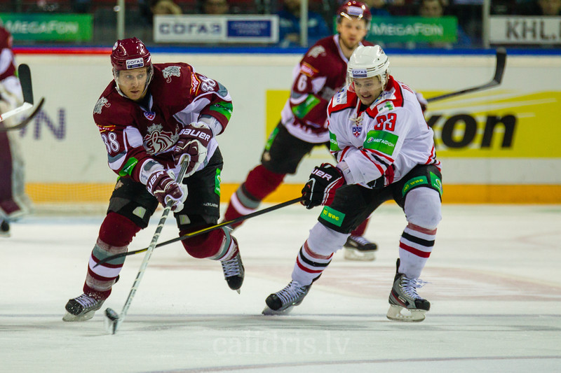 Babchuk Anton (33) tries to block the pass of Paul Szczechura (38) during KHL regular championship game between Dinamo Riga and Donbass Donetsk in Arena Riga