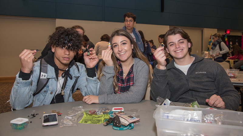Isaac Moreno (left), Maya Alshakhshir, and Chandler Gibbs put together Lego figurines during Paws on the Island.