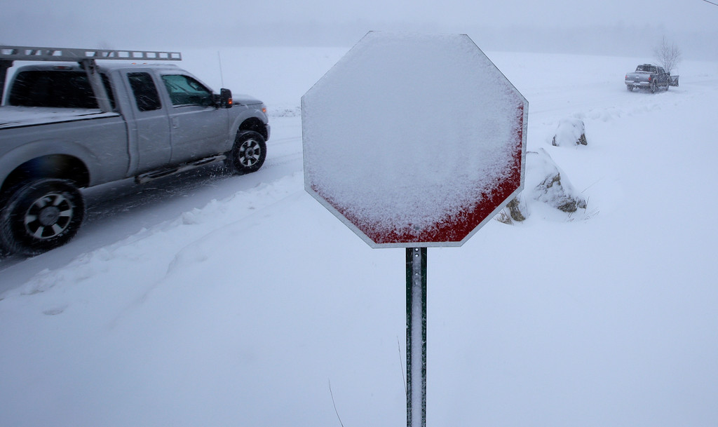 . Wind blown snow covers a stop sign as four wheel drive pick-up trucks pass during a winter storm in Derry, N.H., Tuesday, March 13, 2018. The nor\'easter is expected to deliver up to 2 feet of snow to some areas of New England, bringing blizzard conditions to parts of coastal Massachusetts and covering highways with snow. (AP Photo/Charles Krupa)