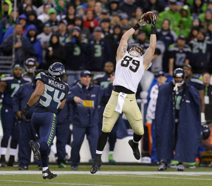 . New Orleans Saints tight end Josh Hill, right, catches a pass next to Seattle Seahawks middle linebacker Bobby Wagner (54) during the second half of an NFC divisional playoff NFL football game in Seattle, Saturday, Jan. 11, 2014. (AP Photo/Ted S. Warren)