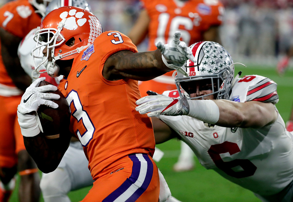 . Clemson wide receiver Artavis Scott (3) is tackled by Ohio State defensive end Sam Hubbard (6) during the first half of the Fiesta Bowl NCAA college football game, Saturday, Dec. 31, 2016, in Glendale, Ariz. (AP Photo/Rick Scuteri)