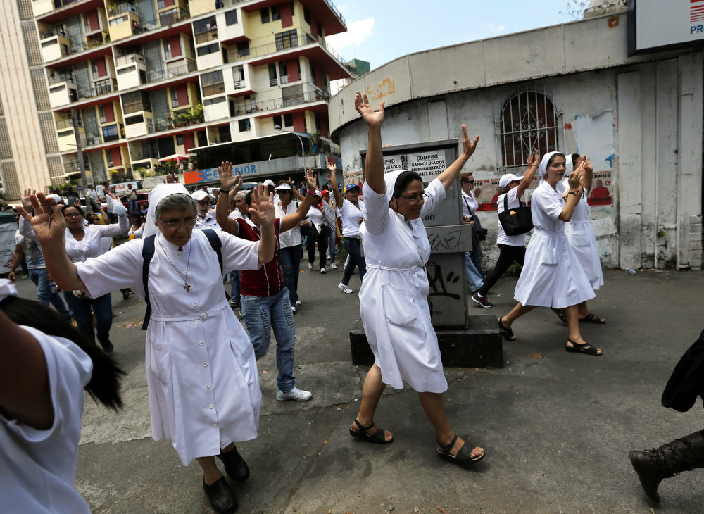 . Nuns raise their arms during a women\'s march protesting repression against anti-government demonstrators in Caracas, Venezuela, Wednesday, Feb. 26, 2014. Former U.S. President Jimmy Carter is expressing concern about Venezuela\'s escalating political crisis and wants to meet with leaders on both sides in an upcoming trip.(AP Photo/Fernando Llano)