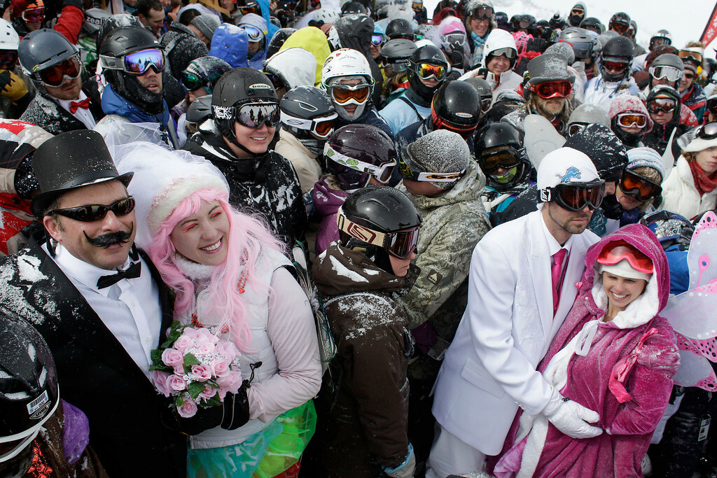 . Eighty-eight couples gather in a blizzard atop a mountain to get married or renew their vows, at the 22nd Annual Marry Me & Ski Free Mountaintop Matrimony, at Loveland Ski Area, in Colorado, Thursday, Feb. 14, 2013. At left are couple Joseph and Elizabeth Antonio, who renewed their vows after six years of marriage, and at right are newlyweds Mary Stipe and Ryan Kargol. (AP Photo/Brennan Linsley)