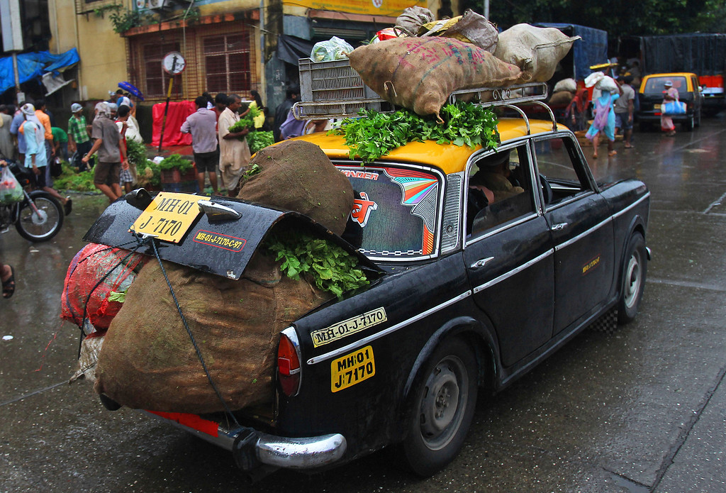 . A  Premier Padmini taxi is overloaded with vegetables as it drives through a street in Mumbai, India, Friday, Aug 2, 2013. More than 4500 Premier Padmini taxis are expected to be banned from the roads in Mumbai this year, starting in August,  in line with a government order that bans cabs that are more than 20 years old. (AP Photo/Rafiq Maqbool)