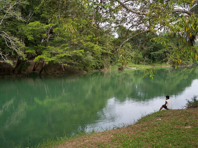 Man sitting at riverside, Chaa Creek Road, Chaa Creek Nature Reserve, San Ignacio, Belize