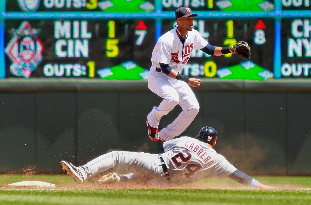 . Twins shortstop Pedro Florimon jumps over Detroit\'s Miguel Cabrera as he completes a double play during the fifth inning. (AP Photo/Genevieve Ross)