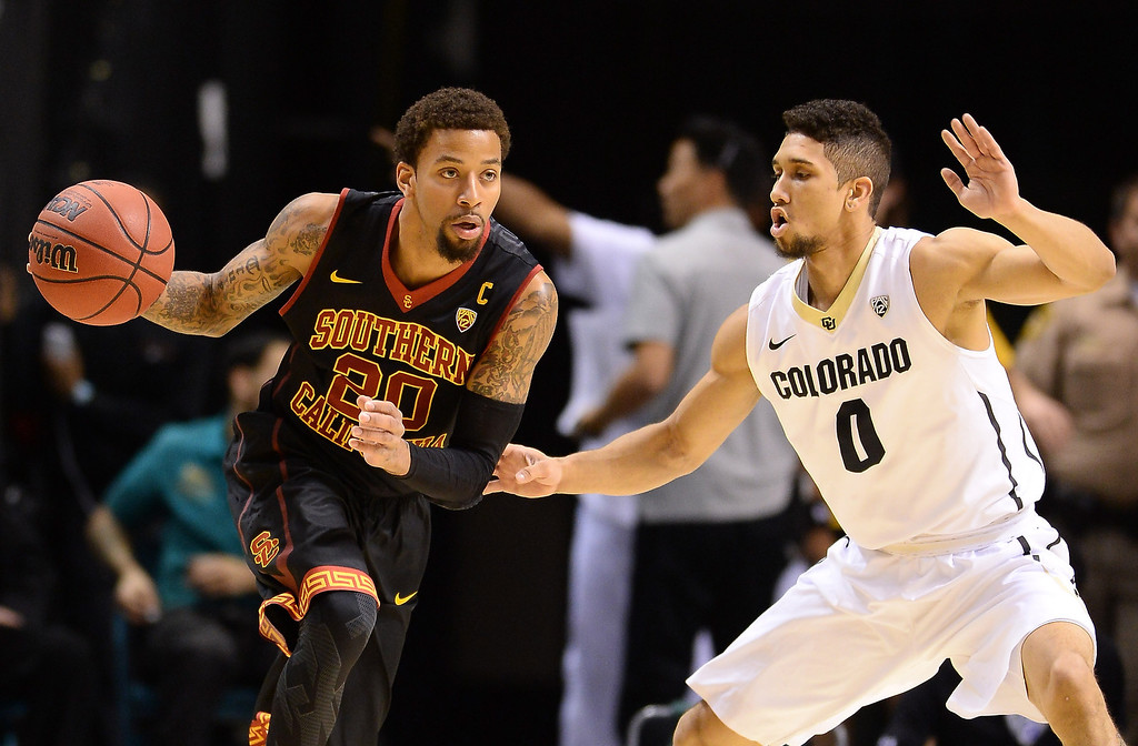 . J.T. Terrell #20 of the USC Trojans is guarded by Askia Booker #0 of the Colorado Buffaloes during a first-round game of the Pac-12 Basketball Tournament at the MGM Grand Garden Arena on March 12, 2014 in Las Vegas, Nevada.  (Photo by Ethan Miller/Getty Images)