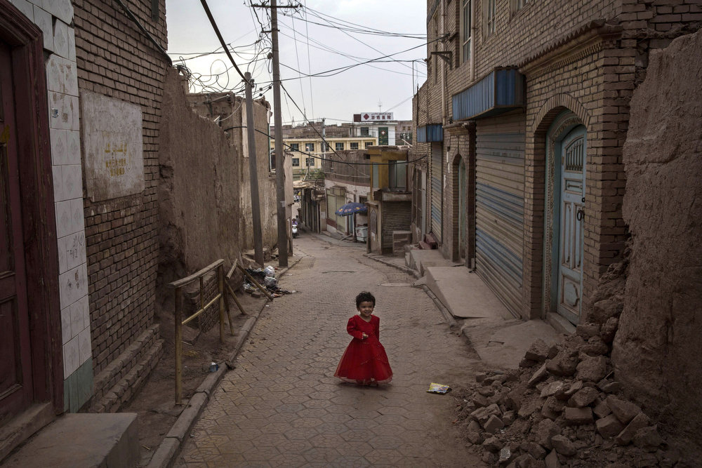 . KASHGAR, CHINA - JULY 29: A Uyghur wears a gown as she walks on the Eid holiday on July 29, 2014 in alleyway in old Kashgar, Xinjiang Province, China. Nearly 100 people have been killed in unrest in the restive Xinjiang Province in the last week in what authorities say is terrorism but advocacy groups claim is a result of a government crackdown to silence opposition to its policies. China\'s Muslim Uyghur ethnic group faces cultural and religious restrictions by the Chinese government. Beijing says it is investing heavily in the Xinjiang region but Uyghurs are increasingly dissatisfied with the influx of Han Chinese and uneven economic development.  (Photo by Kevin Frayer/Getty Images)
