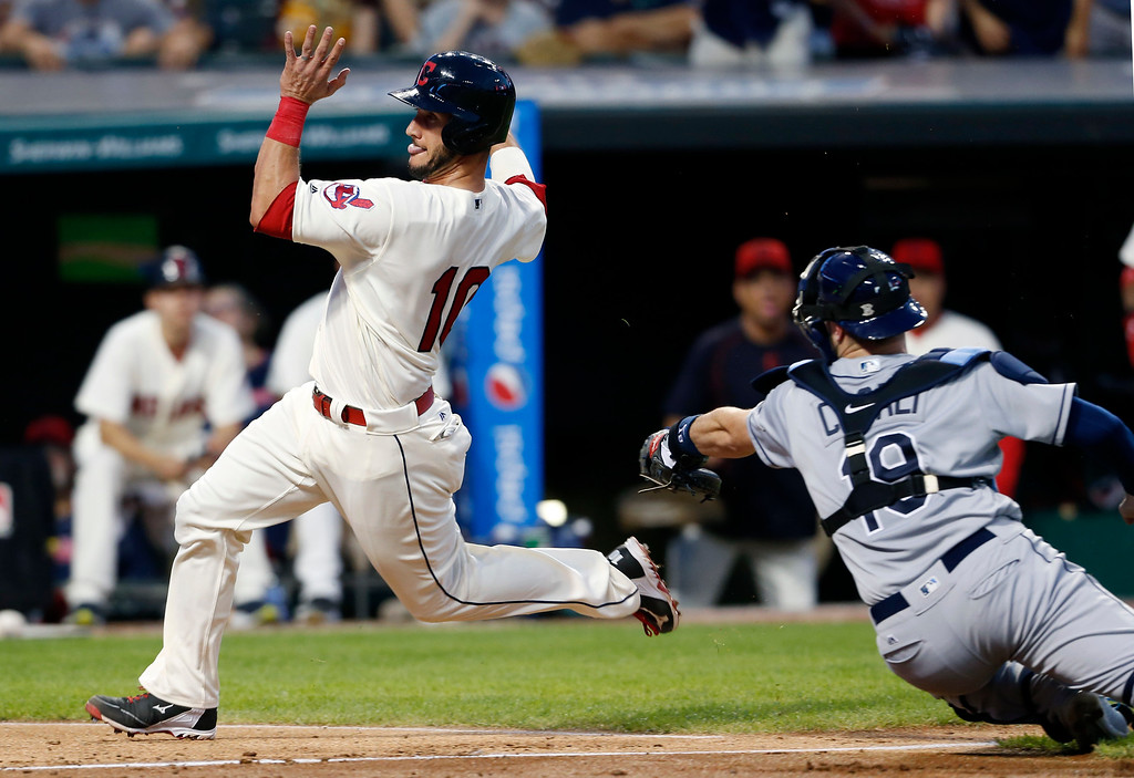 . Cleveland Indians\' Yan Gomes (10) scores past Tampa Bay Rays catcher Curt Casali (19) on a sacrifice fly by Rajai Davis during the seventh inning of a baseball game, Monday, June 20, 2016, in Cleveland. (AP Photo/Ron Schwane)