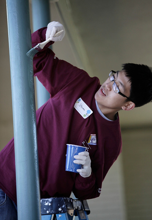 . Kaiser Permanente volunteer, Steven Tran, paints poles at Ryan Elementary School during a Dr. Martin Luther King Jr. day-of-service activity in San Jose, Calif. on Monday, January 21, 2013.   (Gary Reyes/ Staff)