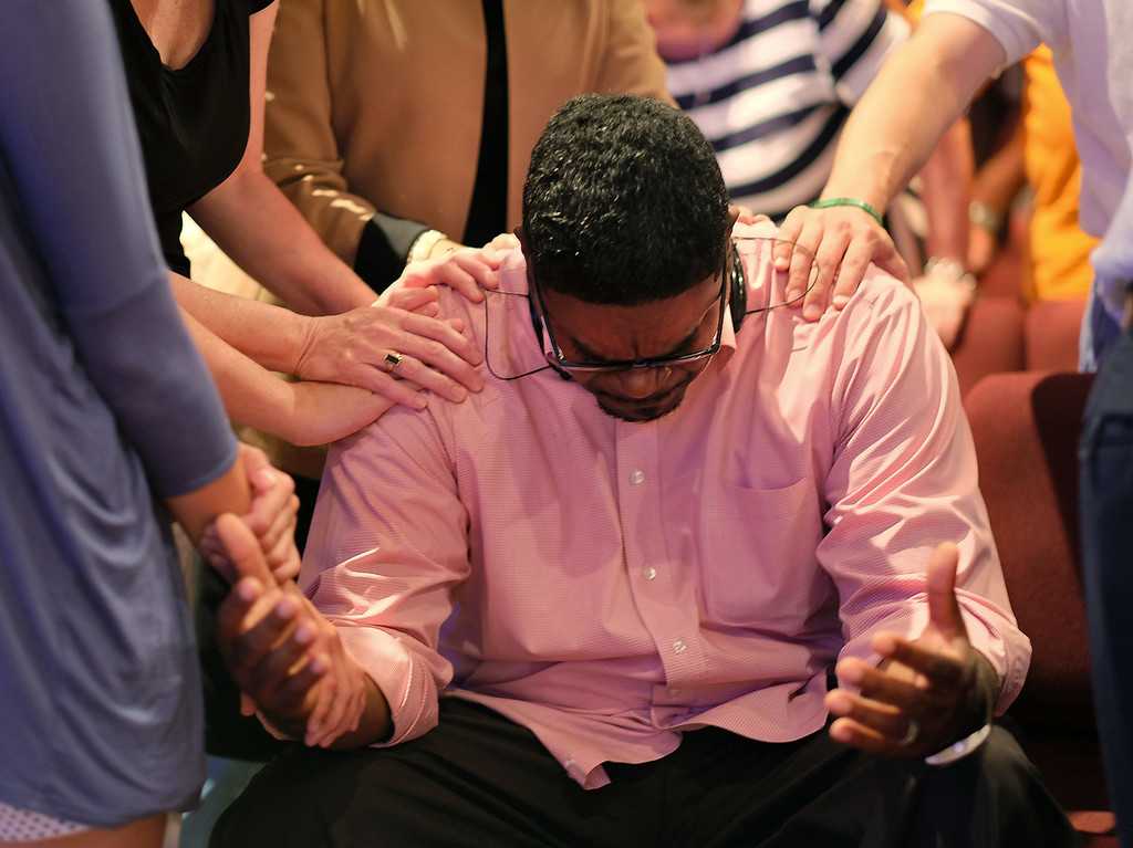 . Keith McDaniel, pastor of Macedonia Missionary Baptist Church, is surrounded by others in prayer for the victims of Wednesday\'s shooting at Emanuel AME Church in Charleston, S.C., Thursday, June 18, 2015 at Anderson Mill Road Baptist Church in Spartanburg. Dylann Storm Roof, 21, was arrested Thursday in the slayings of several people, including the church\'s pastor, at a prayer meeting inside the historic black church in downtown Charleston. (Tim Kimzey/The Spartanburg Herald-Journal via AP)