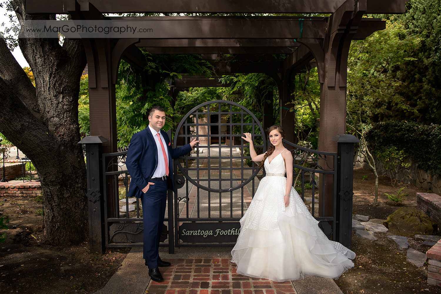 full body portrait of bride and groom standing in front of Saratoga Foothill Club gate