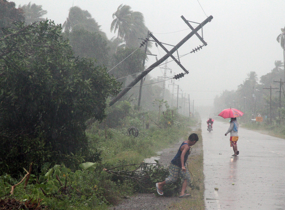 . Residents brave heavy rains next to a tilted electric post after Typhoon Bophal hit the city of Tagum, Davao del Norter province, in southern island of Mindanao on December 4, 2012.  Typhoon Bopha smashed into the southern Philippines early December 4, as more than 40,000 people crammed into shelters to escape the onslaught of the strongest cyclone to hit the country this year.     AFP PHOTOSTR/AFP/Getty Images