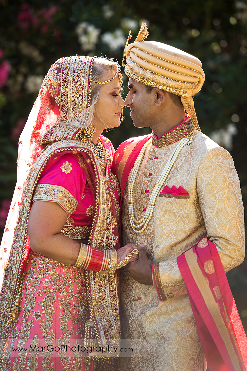 Indian bride and groom in golden and pink outfits touching heads at Elliston Vineyards in Sunol