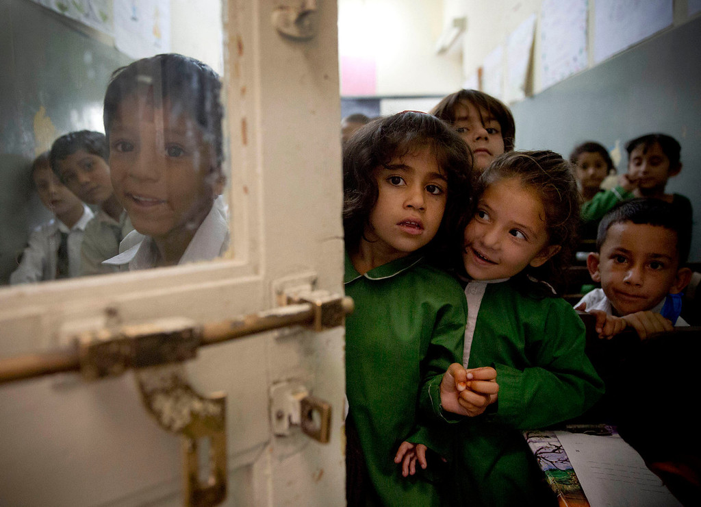 . Pakistani children peek through a door as they attend class in a school in Mingora, Swat Valley, Pakistan on Saturday, Oct. 5, 2013. Malala Yousufzai\'s battle for girls\' education began when she was barely 11 years old and at a time when the Taliban roamed freely throughout the valley, blowing up schools, beheading security forces and leaving their dismembered bodies in the town square. (AP Photo/Anja Niedringhaus)